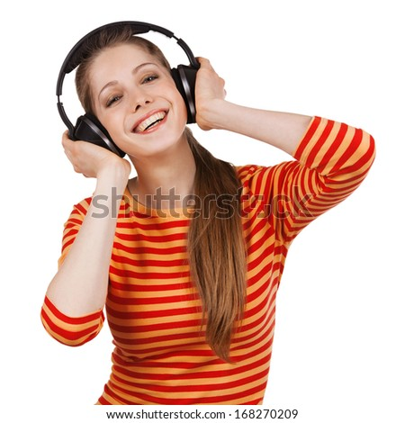 Beautiful cheerful girl with headphones listening to music - stock photo