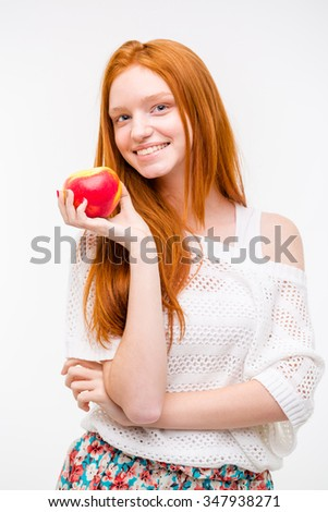 Beautiful cheerful happy attractive natural girl with long red hair holding an apple