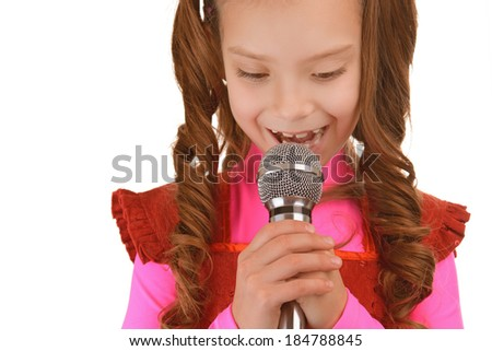 Beautiful cheerful little girl in red dress singing into microphone, isolated on white background. - stock photo