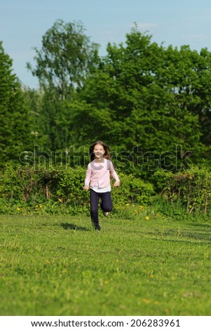 Beautiful cheerful little girl runs across the grass with long hair flying outdoor