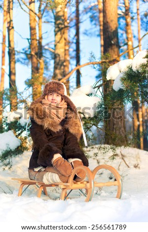 Beautiful cheerful little girl sitting on sledges in winter forest. Contemplating nature. Winter outdoors. - stock photo