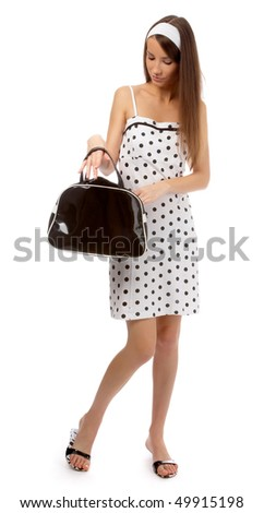 beautiful cheerful model in polka-dot dress is trying to find something in her black bag - stock photo