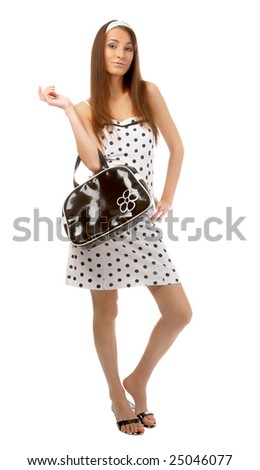 beautiful cheerful model poses in polka-dot dress with black bag on white - stock photo