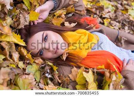 Beautiful cheerful red-haired woman lying in autumn leaves wearing bright yellow scarf