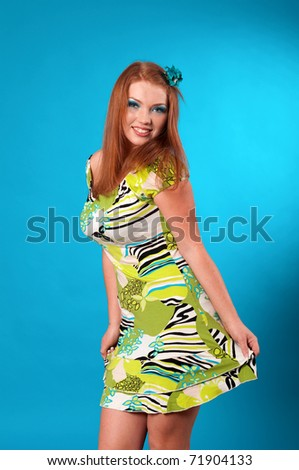 beautiful  cheerful redhead woman posing on blue background - stock photo
