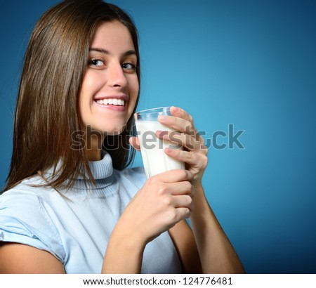 beautiful cheerful teen girl drinking milk over blue background - stock photo