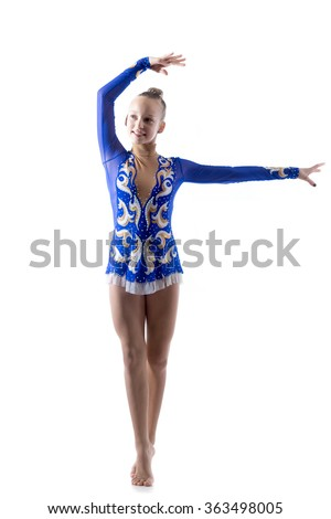 Beautiful cheerful teenage elegant performer girl wearing dancer blue leotard working out, dancing, posing, doing artistic gymnastics exercise, full length, studio, white background, isolated - stock photo