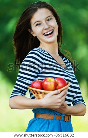 beautiful cheerful woman long hair holding basket apples summer park - stock photo