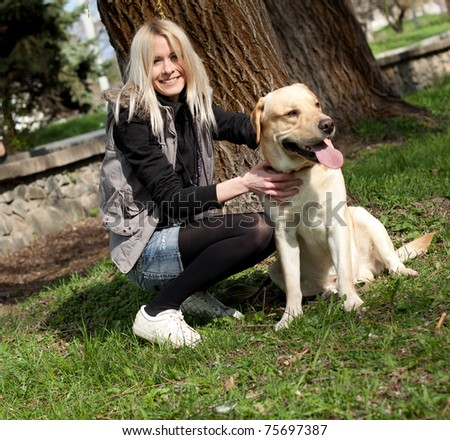 Beautiful cheerful woman sitting with her dog in the park - stock photo
