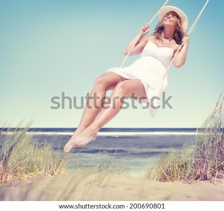 Beautiful Cheerful Woman Swinging by the Beach - stock photo