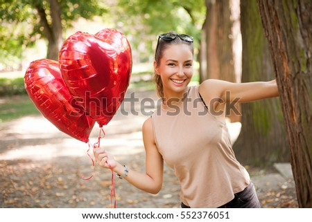 Beautiful cheerful young brunette woman with read heart balloons.