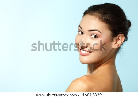 beautiful cheerful young woman, beauty female face happy smiling and looking at camera over blue background - stock photo