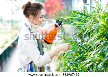 Beautiful cheerful young woman gardener in colorful apron spraying flowers and plants using water pulverizer in garden center - stock photo