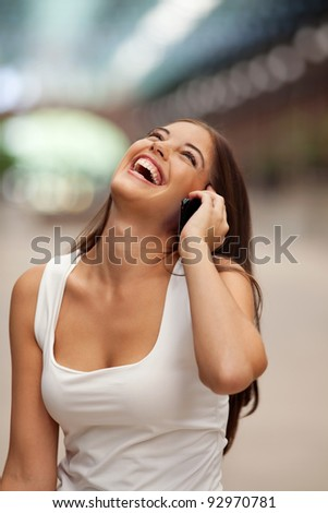 Beautiful cheerful young woman talking on phone
