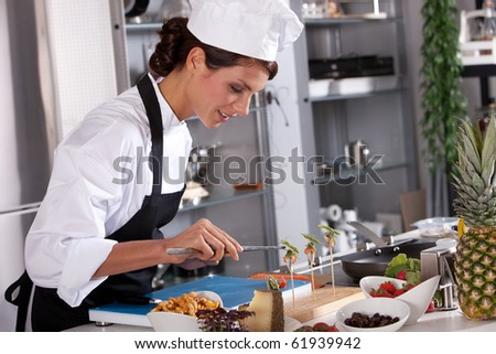Beautiful chef preparing an amuse with pincers - stock photo