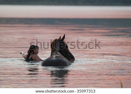 beautiful chestnut Russian Don gelding and the girl swimming in the water at sunrise