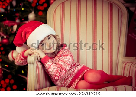 Beautiful child against Christmas tree. Little girl dressed in Santa Claus hat. Baby at home. Xmas holiday concept - stock photo