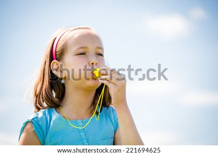 Beautiful child blowing in whistle - outdoor with blue sky - stock photo