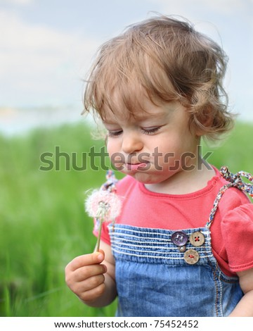 Beautiful child blows on dandelion in the summer. Shallow depth of field - stock photo