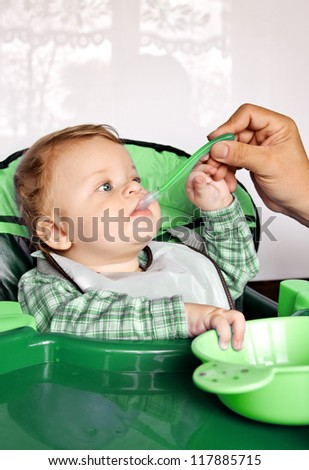 Beautiful child boy is feeding by his father - stock photo