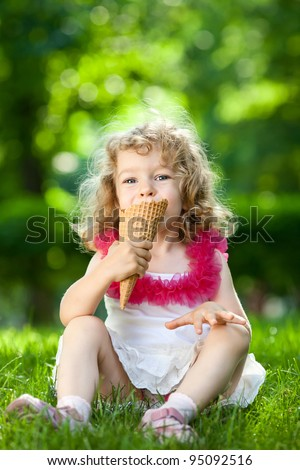Beautiful child eating ice-cream outdoors in spring park against natural green background - stock photo