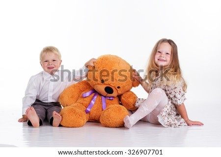 Beautiful child girl and boy are embracing big brown teddy bear, isolated on white