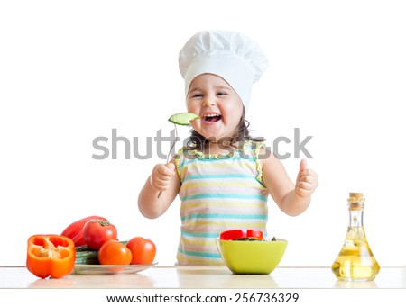 beautiful child girl in cook hat eating vegetables