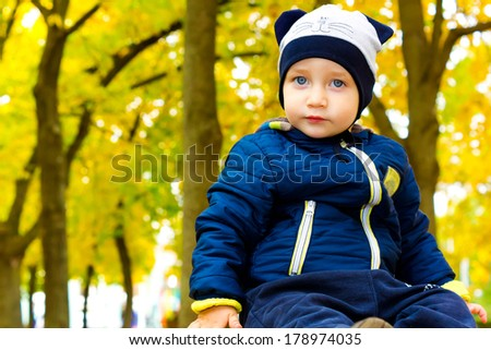 Beautiful child in a funny hat in autumn Park - stock photo