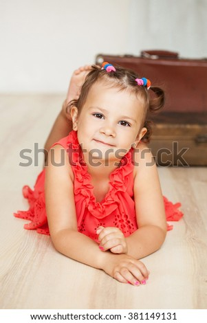 beautiful child in a red dress lying on the floor - stock photo