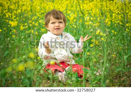 beautiful child in canola field - stock photo
