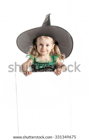 Beautiful child in Halloween witch costume with hat holding an empty board for advertisement