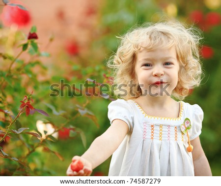 Beautiful child in summer garden - stock photo