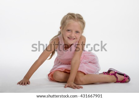 Beautiful child in the foreground sits on the white ground and leans on her hands. Blonde with plaited hair looks in the camera with spread smile. - stock photo