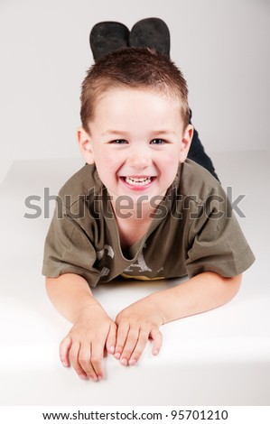 beautiful child laying down and smiling - stock photo