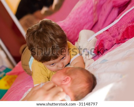 beautiful child looks at his newborn brother - stock photo