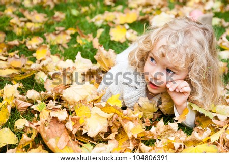 Beautiful child lying on yellow maple leaves in autumn park - stock photo