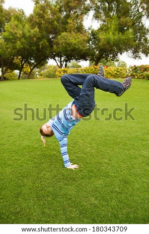 Beautiful child playing on green grass in a park jumping and walking on his arms - stock photo