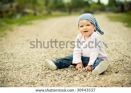 beautiful child plays on a stones road - stock photo