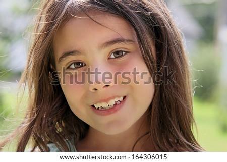 Beautiful child portrait smiling outside. - stock photo