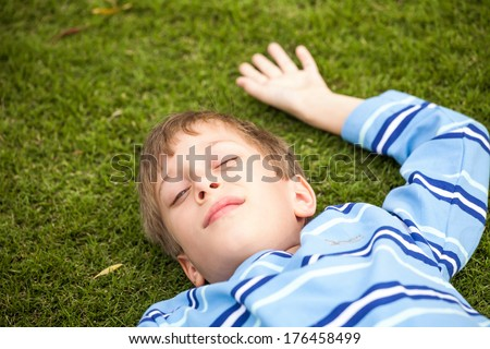Beautiful child relaxing on green grass in a park with his eyes closed - stock photo