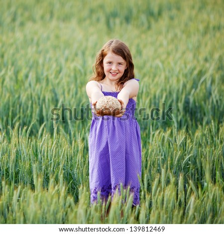 Beautiful child showing bread over the cornfield landscape - stock photo