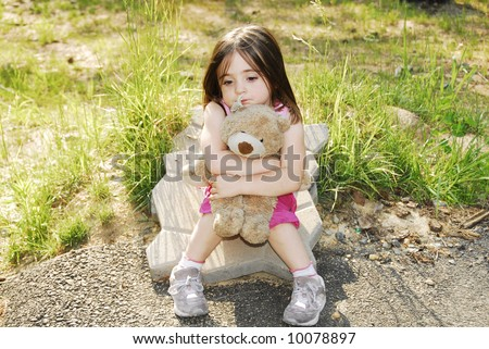 Beautiful child sitting hugging her very best friend and playmate her stuffed bear. - stock photo