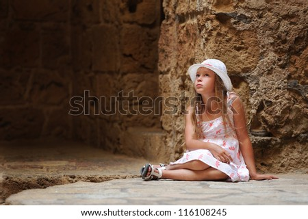beautiful child sitting in a cave - stock photo