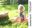 Beautiful child sitting on grass in summer park - stock photo