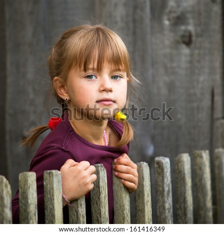 Beautiful child standing near vintage rural fence. - stock photo