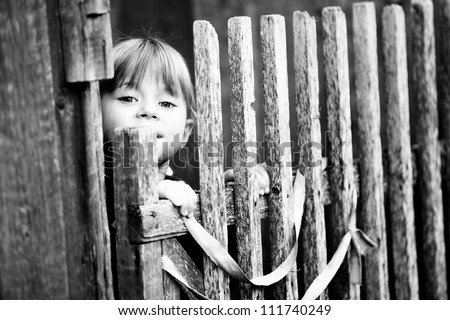 Beautiful child standing near vintage rural fence (Black-and-white photo with high contrast) - stock photo