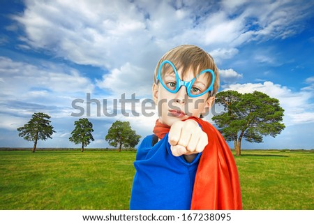 Beautiful child superhero protecting nature standing on green field (environment protection concept)  - stock photo