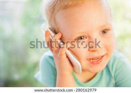 Beautiful child talking by mobile phone with her mother. Girl is blonde with very beautiful eyes on a green background and she is happy - stock photo