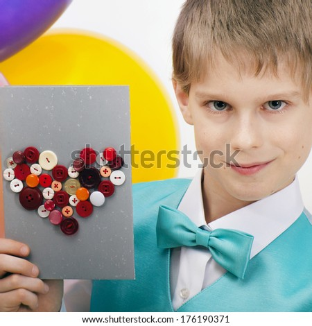 Beautiful child with balloons and postcard of Valentine's Day with a red heart