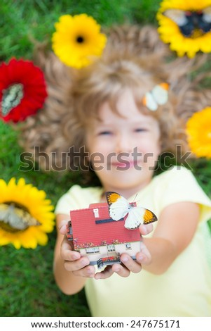Beautiful child with butterfly in spring park. Happy kid holding house in hand. Real estate concept. Unusual top view portrait - stock photo